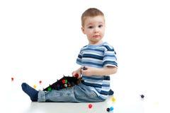Muchacho lindo del niño que juega con el juguete del mosaico Imagen de archivo libre de regalías