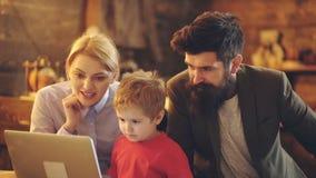 Muchacho lindo del pequeño niño que mira historietas de observación de la pantalla del ordenador portátil con los padres en casa  metrajes