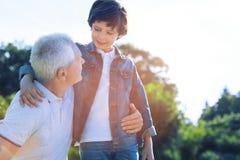Muchacho lindo del preadolescente que habla con el abuelo cariñoso al aire libre Imagenes de archivo