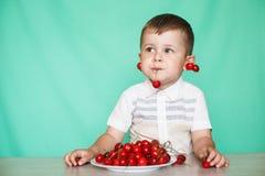 Muchacho lindo del muchacho que come cerezas maduras, haciendo caras divertidas y jugando con las cerezas, divirtiéndose fotografía de archivo