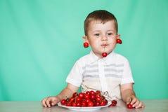 Muchacho lindo del muchacho que come cerezas maduras, haciendo caras divertidas y jugando con las cerezas, divirtiéndose fotos de archivo libres de regalías