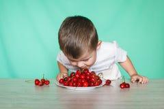 Muchacho lindo del muchacho que come cerezas maduras, haciendo caras divertidas y jugando con las cerezas, divirtiéndose imagen de archivo libre de regalías