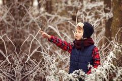 Muchacho lindo del retrato en bosque caliente del invierno Imagenes de archivo