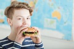 Muchacho lindo delante del mapa mientras que come una hamburguesa Imágenes de archivo libres de regalías