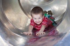 Muchacho lindo, deslizando abajo la diapositiva, sonriendo Foto de archivo