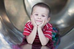 Muchacho lindo, deslizando abajo la diapositiva, sonriendo Fotos de archivo libres de regalías
