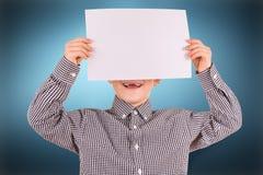 Muchacho lindo divertido con la hoja de papel blanca Imagenes de archivo
