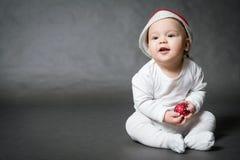 Muchacho lindo en el sombrero de Papá Noel que sostiene la bola de la Navidad Fotos de archivo libres de regalías