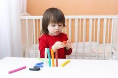 Muchacho lindo en la camisa roja que juega con el playdough Fotografía de archivo libre de regalías