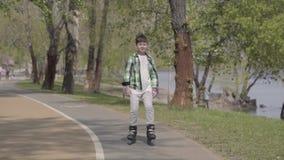 Muchacho lindo en la ropa brillante rollerblading en el parque cerca del r?o Ocio al aire libre El ni?o que se divierte solamente almacen de metraje de vídeo