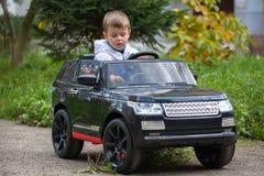 Muchacho lindo en montar un coche eléctrico negro en el parque fotos de archivo