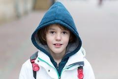 Muchacho lindo en su manera a la escuela en un día frío Imagenes de archivo