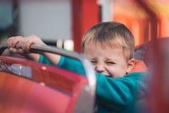 Muchacho lindo en un coche del carrusel Fotografía de archivo libre de regalías