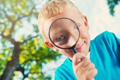 Muchacho lindo en un parque con una lupa Imagen de archivo libre de regalías