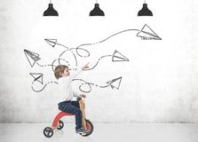 Muchacho lindo en un triciclo, mostrando los aviones de papel Imagen de archivo