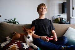 Muchacho lindo feliz que juega la consola del videojuego asentada en un sofá con cierre del perrito del perro del basenji en sala foto de archivo