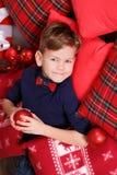 Muchacho lindo hermoso que celebra la Navidad del Año Nuevo solamente cerca del árbol de Navidad en la almohada roja que presenta Foto de archivo libre de regalías