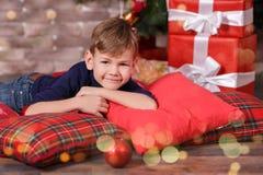 Muchacho lindo hermoso que celebra la Navidad del Año Nuevo solamente cerca del árbol de Navidad en la almohada roja que presenta Fotos de archivo libres de regalías