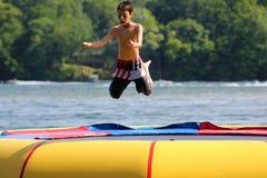 Muchacho lindo hermoso que salta en un trampolín del agua que flota en un lago en Michigan durante verano Fotos de archivo