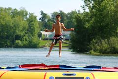 Muchacho lindo hermoso que salta en un trampolín del agua que flota en un lago en Michigan durante verano Fotografía de archivo