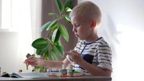 Muchacho lindo 6 a?os que juegan con los ladrillos pl?sticos coloridos del juguete en la tabla en casa metrajes
