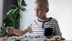Muchacho lindo 6 a?os que juegan con los ladrillos pl?sticos coloridos del juguete en la tabla en casa almacen de video