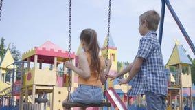 Muchacho lindo que balancea en una muchacha hermosa del oscilación con el pelo largo, sonriendo Un par de niños felices Niños des almacen de metraje de vídeo