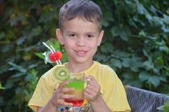 Muchacho lindo que bebe el smoothie sano del zumo de frutas del cóctel en verano Niño feliz que disfruta de la bebida orgánica imágenes de archivo libres de regalías