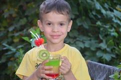 Muchacho lindo que bebe el smoothie sano del zumo de frutas del cóctel en verano Niño feliz que disfruta de la bebida orgánica fotos de archivo libres de regalías