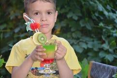 Muchacho lindo que bebe el smoothie sano del zumo de frutas del cóctel en verano Niño feliz que disfruta de la bebida orgánica imagen de archivo