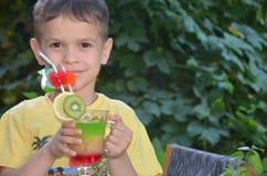 Muchacho lindo que bebe el smoothie sano del zumo de frutas del cóctel en verano Niño feliz que disfruta de la bebida orgánica fotografía de archivo