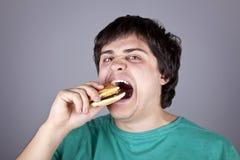Muchacho lindo que come la hamburguesa. Imagen de archivo