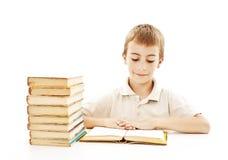 Muchacho lindo que estudia y que lee un libro en su escritorio Imagenes de archivo