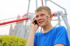 Muchacho lindo que habla un teléfono celular en el parque de atracciones Foto de archivo libre de regalías