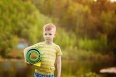 Muchacho lindo que hace deportes en fondo de la naturaleza Niño pequeño deportivo que hace ejercicios en el parque del verano Foto de archivo libre de regalías
