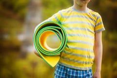 Muchacho lindo que hace deportes en fondo de la naturaleza Niño pequeño deportivo que hace ejercicios en el parque del verano Imagen de archivo