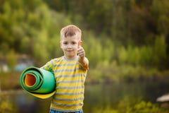 Muchacho lindo que hace deportes en fondo de la naturaleza Niño pequeño deportivo que hace ejercicios en el parque del verano Niñ Imagen de archivo