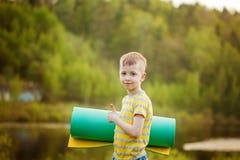 Muchacho lindo que hace deportes en fondo de la naturaleza Niño pequeño deportivo que hace ejercicios en el parque del verano Niñ Fotos de archivo libres de regalías