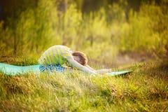 Muchacho lindo que hace deportes en fondo de la naturaleza Niño pequeño deportivo que hace ejercicios en el parque del verano Imagen de archivo libre de regalías