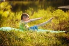 Muchacho lindo que hace deportes en fondo de la naturaleza Niño pequeño deportivo que hace ejercicios en el parque del verano Fotos de archivo