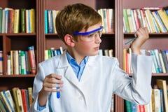Muchacho lindo que hace la investigación de la bioquímica en química Imágenes de archivo libres de regalías