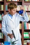 Muchacho lindo que hace la investigación de la bioquímica en química Foto de archivo