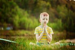 Muchacho lindo que hace yoga en fondo de la naturaleza Niño pequeño deportivo que hace ejercicios en el parque del verano Foto de archivo