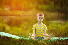 Muchacho lindo que hace yoga en fondo de la naturaleza Niño pequeño deportivo que hace ejercicios en el parque del verano Imágenes de archivo libres de regalías