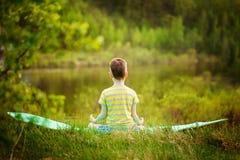 Muchacho lindo que hace yoga en fondo de la naturaleza Niño pequeño deportivo que hace ejercicios en el parque del verano Visión  Fotografía de archivo libre de regalías