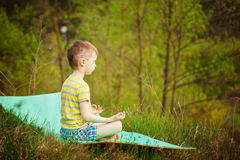 Muchacho lindo que hace yoga en fondo de la naturaleza Niño pequeño deportivo que hace ejercicios en el parque del verano Foto de archivo libre de regalías