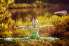 Muchacho lindo que hace yoga en fondo de la naturaleza Niño pequeño deportivo que hace ejercicios en el parque del verano Imagenes de archivo