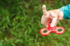 Muchacho lindo que juega con el tri hilandero de la mano de la persona agitada al aire libre Juguete de moda para las manos para  Imágenes de archivo libres de regalías