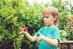 Muchacho lindo que juega con el tri hilandero de la mano de la persona agitada al aire libre Juguete de moda para las manos para  Fotos de archivo
