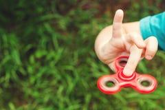 Muchacho lindo que juega con el tri hilandero de la mano de la persona agitada al aire libre Juguete de moda para las manos para  Imagen de archivo